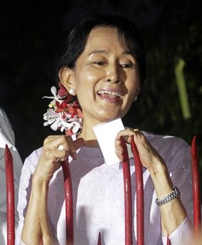 Myanmar's pro-democracy leader Aung San Suu Kyi talks to the supporters as she stands at the gate of her home Saturday, Nov. 13, 2010 in Yangon,