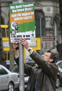 A protester puts up a placard to protest at the visit by Britain's Queen Elizabeth II to Ireland, Monday, May, 16, 2011.  Queen Elizabeth II begins a four day visit to Ireland on Tuesday for the first time since Irish Independence.  (AP Photo/Peter Morrison)